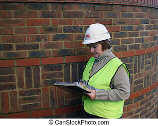 female construction worker with hard hat and clip board, high visibility vest on site