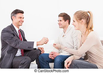 Consultant Giving Visiting Card To Couple - Happy Male...
