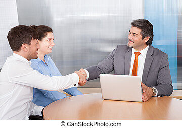 Consultant Shaking Hand With Man - Mature Male Consultant...