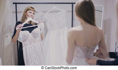 Consultant shows wedding gown in bridal shop - girl and...