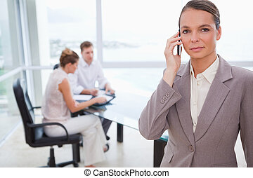 Consultant standing with cellphone