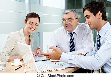 Consulting - A business team of three sitting in office and ...