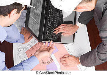 Consulting - Above view of engineers looking at blueprints...