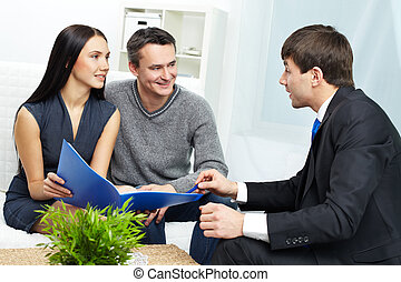 Consulting clients - Portrait of modern couple listening to...