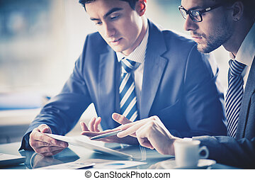 Consulting - Image of two young businessmen discussing ...