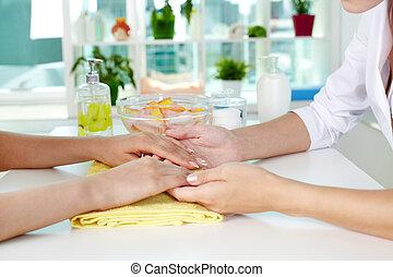 Consulting on manicure - Professional manicurist examining...