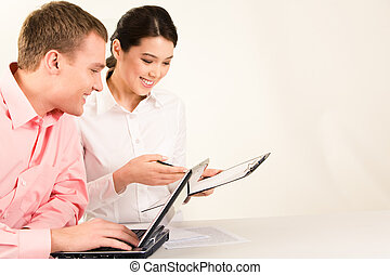 Photo of business partners sitting at workplace and looking at document with smiles