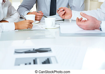 Consulting - Close-up of businesspeople discussing plan at...