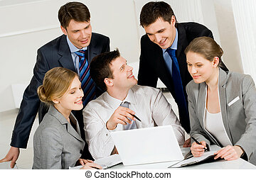 Consulting - Portrait of friendly workteam looking at laptop...