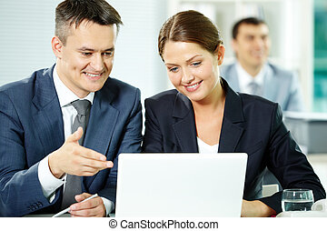 Consulting - Two business partners sitting in office and...