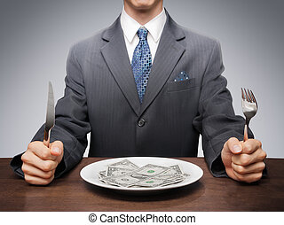 Consumerism - Businessman eating dollar bills from a plate