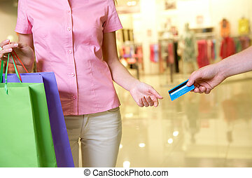 Consumerism - Close-up of woman taking plastic card from...