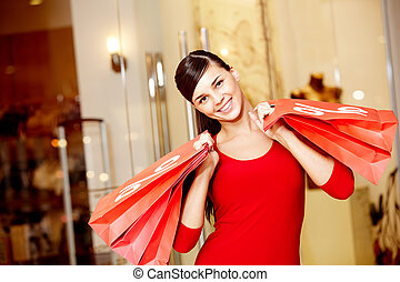 Consumerism - Happy girl holds red paperbags with symbol of...