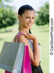 happy young woman smiling with shopping bags