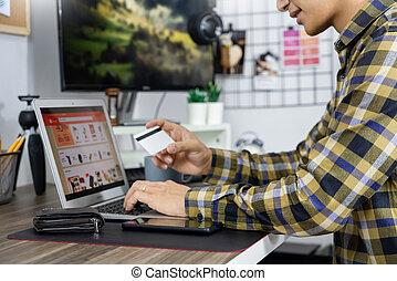 consumidor, concept., tarjeta, seguridad, internet, hogar, hombre, tenencia, asiático, código, credito, computador portatil, entrar, o, comercio en línea, trabajo computadora, compras, banca