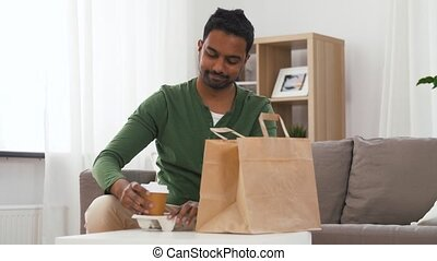 indian man with takeaway coffee and food at home -...
