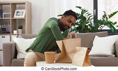 smiling indian man unpacking takeaway food at home -...