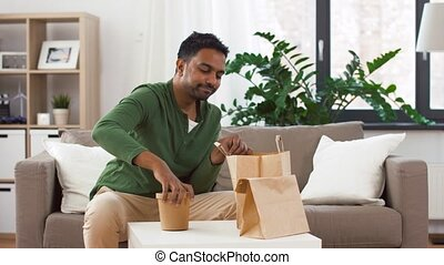 smiling indian man unpacking takeaway food at home - ...