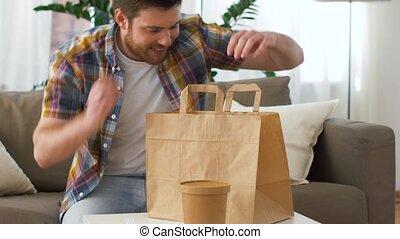 smiling man unpacking takeaway food at home - consumption,...