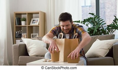 smiling man unpacking takeaway food at home - consumption, ...