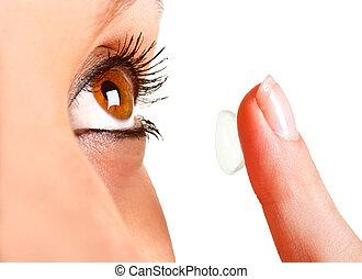 Contact Lens - Closeup of a woman inserting a contact lens...