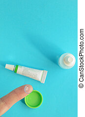 contact lens on finger, tube of eye ointment and small bottle of eye drops on light blue background. Space for text on top, top view.