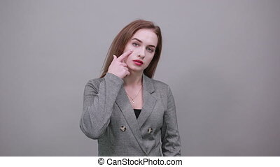 Contact lens on index finger, pointing to eye with hand, thinking, having sensitive eyes, touching herself face by forefinger. Young attractive woman, dressed gray jacket, with green eyes, light brown