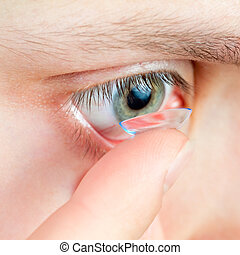 Contact lens - Young woman Inserting a contact lens closeup