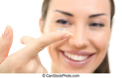 Contact lens on finger of young woman; closeup portrait. Young brunette woman holding contact lens on finger in front of her eye
