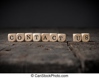 Contact us concept image - Small wooden dices with the words...