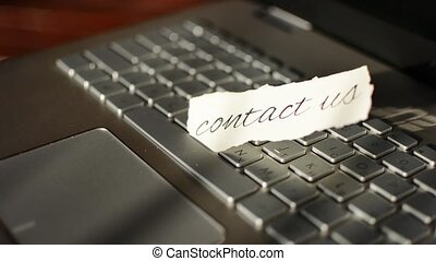 Contact Us. Handmade message with calligraphic text lies on the keyboard