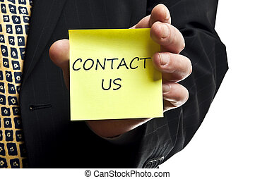 """Business man showing """"Contact Us"""" post it"""