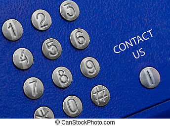 telephone panel with metal buttons and sign contact us