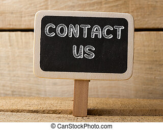 Contact us wooden sign on wood background