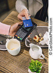 Contactless Cafe Payment - High angle view of a woman making...