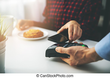 contactless payment - woman paying bill with smartphone at...