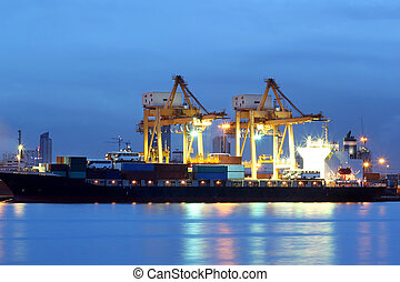 Container Cargo freight ship with working crane at twilight time