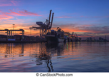 Container Cargo freight ship with working crane bridge in shipyard at dusk for Logistic Import Export background in sunset