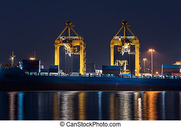 container cargo freight ship with working crane bridge in shipyard at night