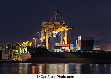 container cargo freight ship with working crane bridge in shipyard at twilight