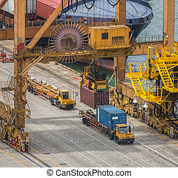 Container Cargo freight ship with working crane loading bridge in shipyard