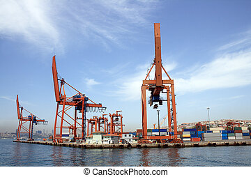 Panorama with blue sky, sea and container harbour. Closeup of few red cranes
