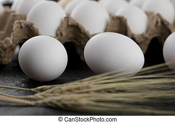 Container of white eggs and ears of wheat on black background