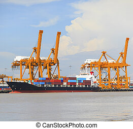 container ship loading goods on port with big crane tool