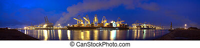 A panoramic image of three container ships being unloaded at night at a busy commercial harbour, with a small trawler moored alongside.