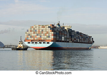 Container ship being brought into port by tug boats,...