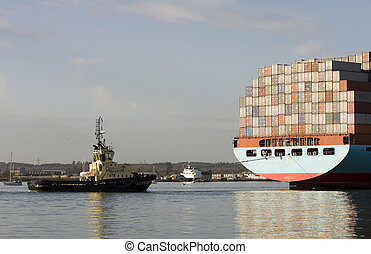 Container ship being brought into port by tug boats, Southampton, England