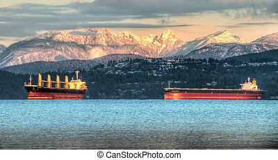 These contain ships sit just off the coast of Vancouver below the white snowy coastal mountain in the background.