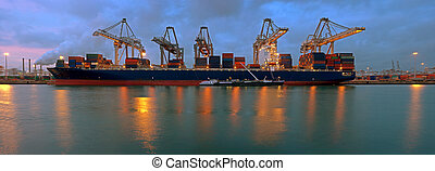 The activity of loading and unloading of huge container ships at the world's biggest and busiest container harbor in Rotterdam, just before sunset
