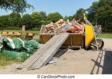 Container with debris and wheelbarrow